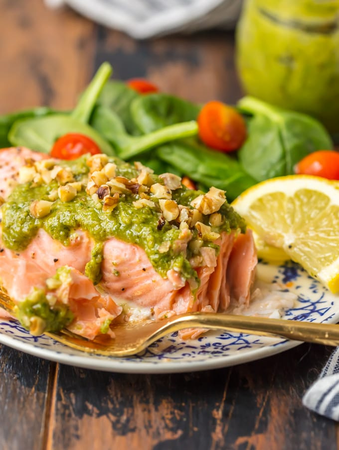 Baked Salmon with Basil Walnut Pesto is our favorite simple yet elegant seafood dinner. This Pesto Salmon Recipe is bursting with flavor and good fat. The tender flakey salmon is basted in butter, white wine, and lemon juice before baking and then topped with an amazing nutty and rich Basil Walnut Pesto. Best Salmon Recipe ever!