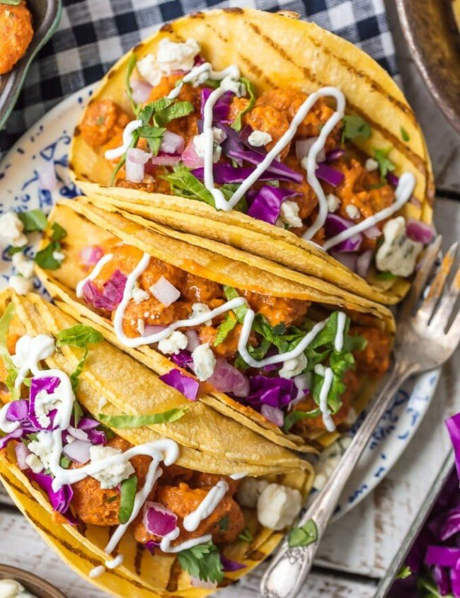 This BUFFALO SHRIMP TACOS RECIPE is tossed in a finger lickin good creamy buffalo sauce and easier than you can even imagine. Perfect for Cinco De Mayo, family night in, or game night with friends! Nothing is better than spicy crispy popcorn shrimp topped with all the fixings and wrapped in a corn tortilla. I'm obsessed.