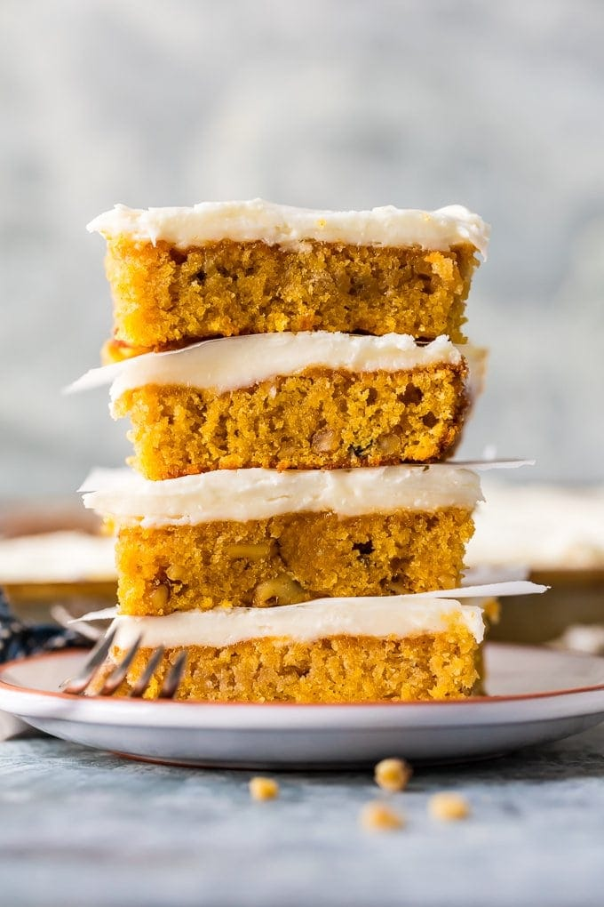 carrot cake bars with cream cheese icing stacked on plate