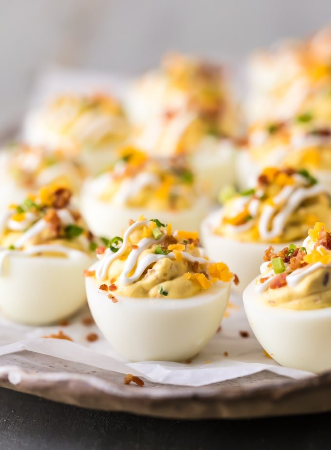 loaded deviled eggs garnished with cheese, sour cream, chives, and bacon