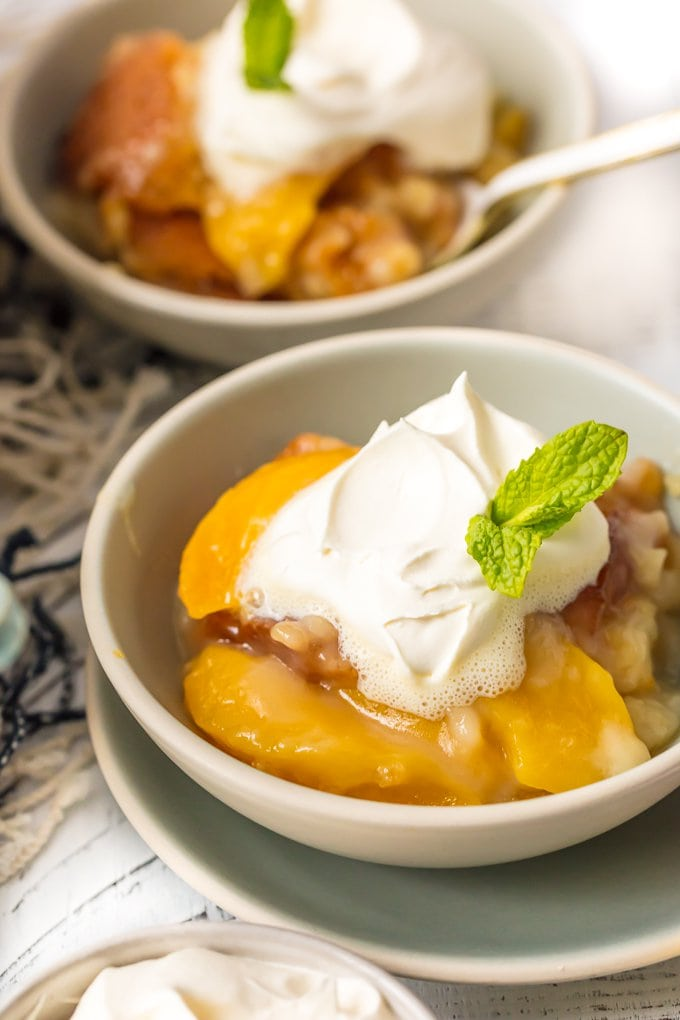 homemade peach cobbler recipe in bowls with cream