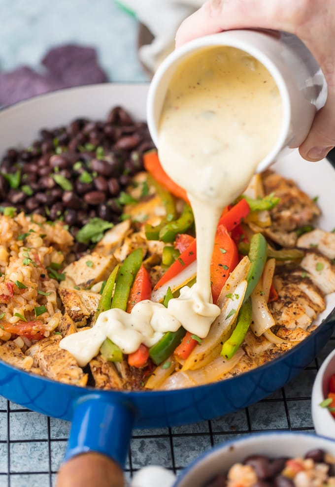 Queso Smothered Chicken Fajitas have quickly become my favorite Chicken Fajita Recipe! Traditional juicy Chicken Fajitas with all the veggies and spice, grilled to perfection, and smothered in cheese dip. This unique twist on a classic Mexican recipe is sure to please one and all and be requested again and again. Serve with rice and beans and know this is better than any Mexican Restaurant meal!
