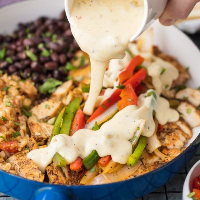 Chicken Fajitas have quickly become a favorite around here, especially this Queso Smothered Chicken Fajita Recipe! Traditional juicy Chicken Fajitas with all the veggies and spice, grilled to perfection, and smothered in cheese dip. This unique twist on a classic Mexican recipe is sure to please one and all and be requested again and again. Better than any Mexican Restaurant meal!