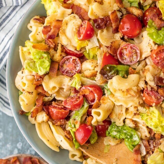 blt pasta salad in a bowl with wooden spoon