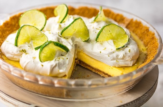 key lime pie topped with whipped cream and lime slices on a cake stand