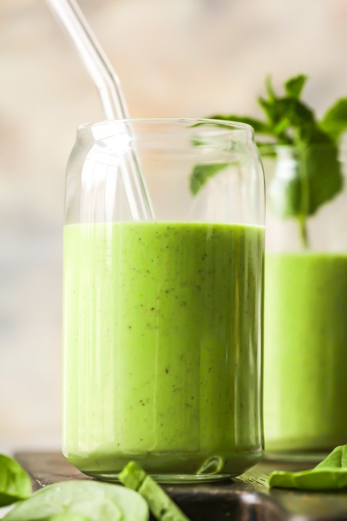 close up of green smoothie in a glass with a glass straw