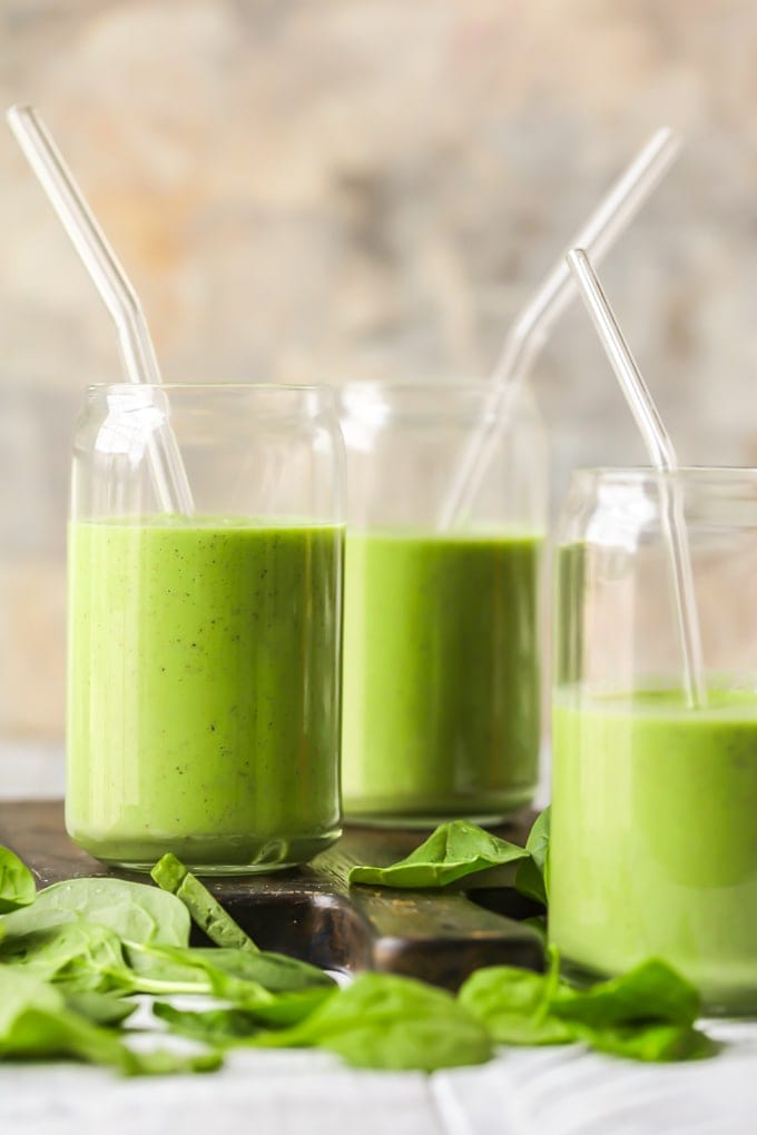 green detox smoothies in glasses on a wooden cutting board