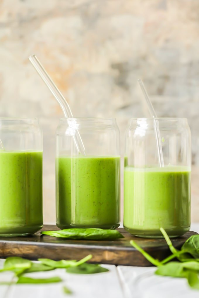 creamy green smoothies on a wooden cutting board