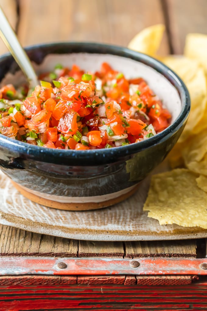 a bowl of pico de gallo with a spoon