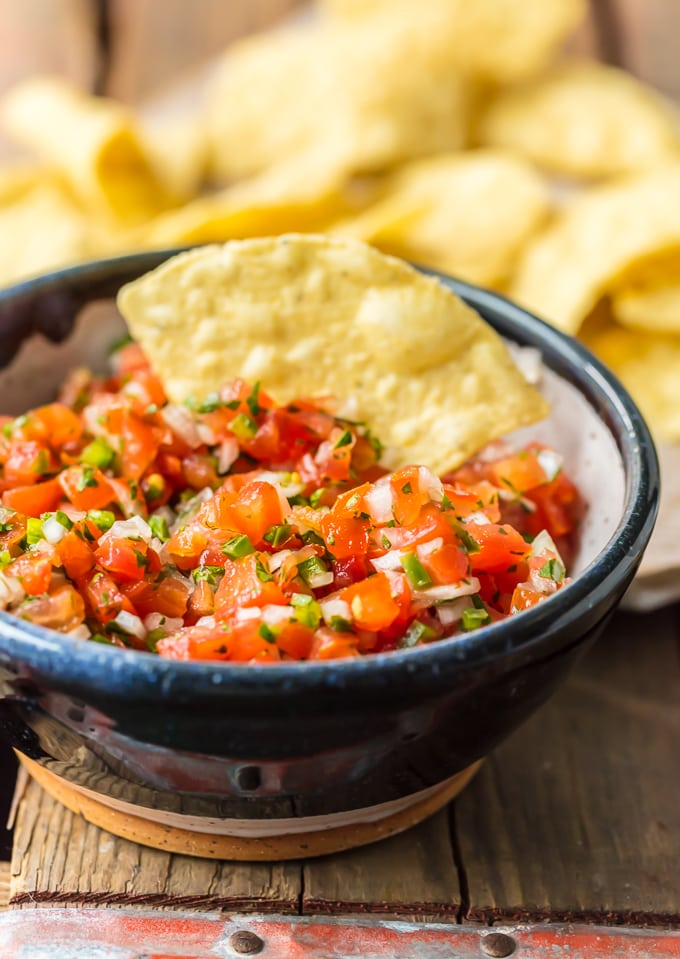fresh pico de gallo in a bowl with a tortilla chip