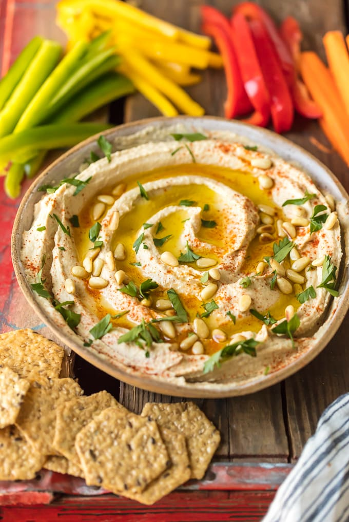 A bowl of homemade hummus next to colorful peppers and crackers