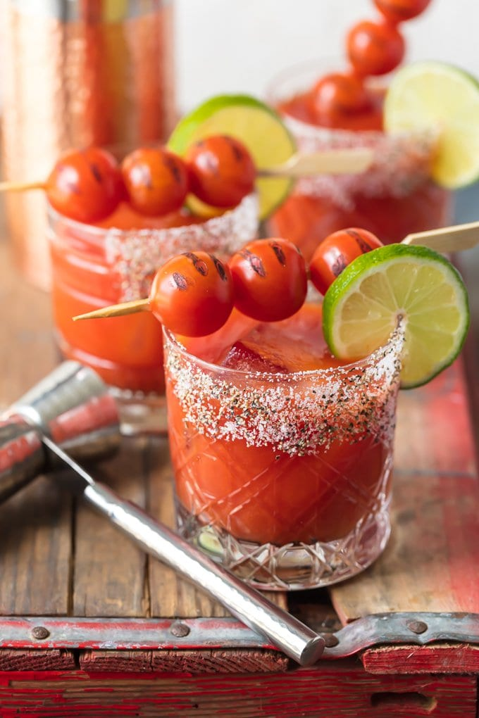 3 tomato margaritas in short glasses, topped with cherry tomatoes