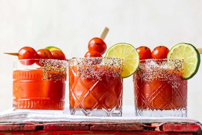 3 short glasses with salt and chili powder rims, filled with tomato margaritas