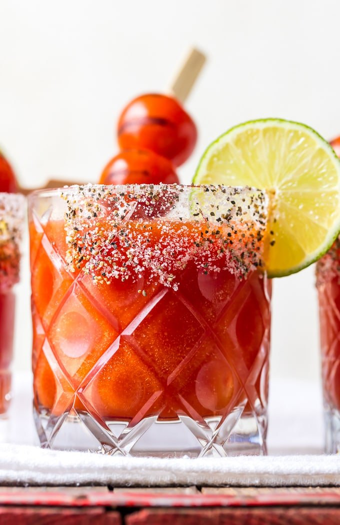 A glass of tomato margarita with a salted rim
