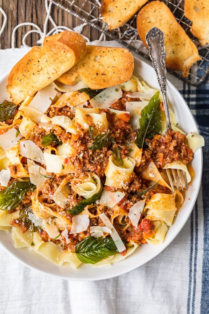 The best bolognese sauce recipe served on a bed of pasta with basil and cheese