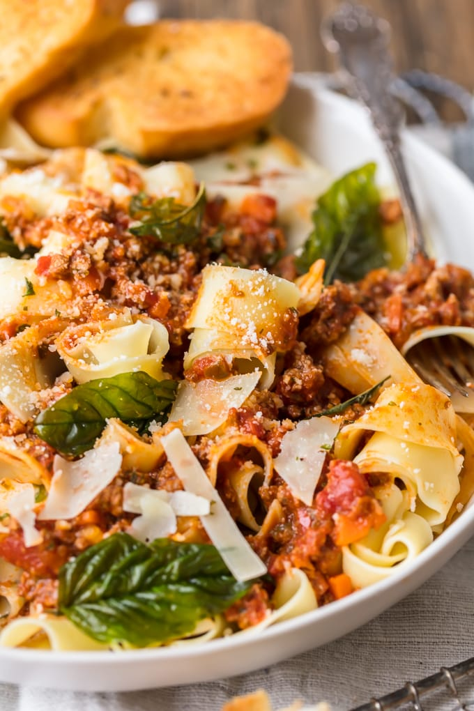 Bolognese sauce mixed with pasta, fresh grated cheese, and basil