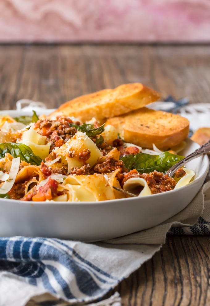 A bowl of pasta bolognese served with bread