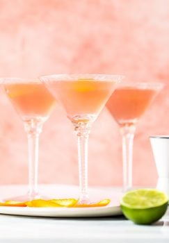 three glasses with cosmos inside beside a cut lime