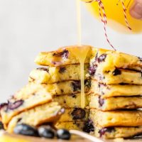 Blueberry Pancakes just might be the most comforting breakfast ever. It's hard not to think of weekend mornings at home with the family when chowing down on pancakes, and that's exactly what this recipe is for! If you want o know how to make blueberry pancakes, it's simple! This is a classic blueberry pancake recipe, light, fluffy, and fruity. And to top it all off, there's a tasty homemade Lemon Sauce to pour on top!