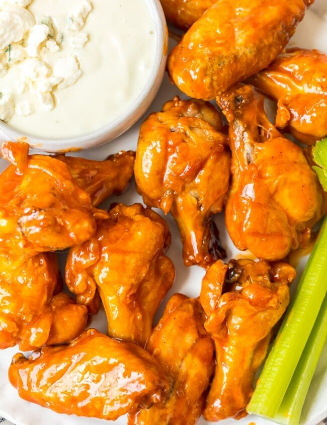 Baked Buffalo Wings are a tasty alternative to typical fried buffalo wings (and a bit healthier too!). These crispy baked chicken wings are covered in our homemade buffalo sauce for the perfect hot and spicy flavor. Baked Buffalo Chicken Wings are a real crowd pleaser and perfect for game day parties. You're going to love these crispy oven baked buffalo wings!