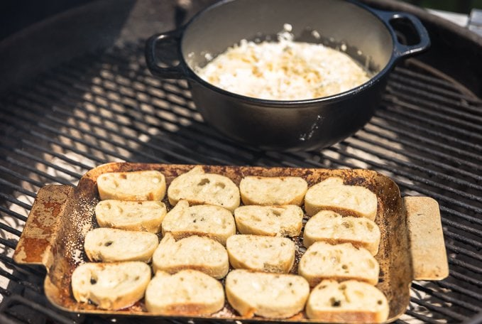 sliced french bread on a pan with cheese fondue on a pot inside of a grill