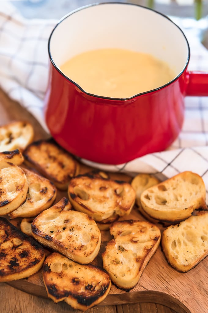 cheese fondue and toasted bread on a cutting board