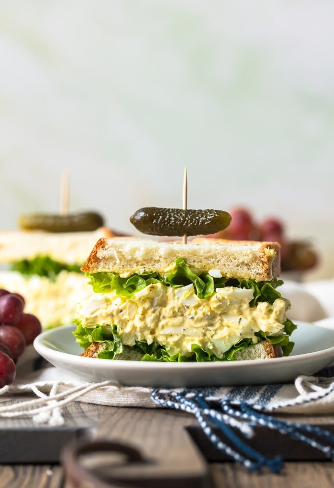 Egg Salad on bread with lettuce and a pickle on top
