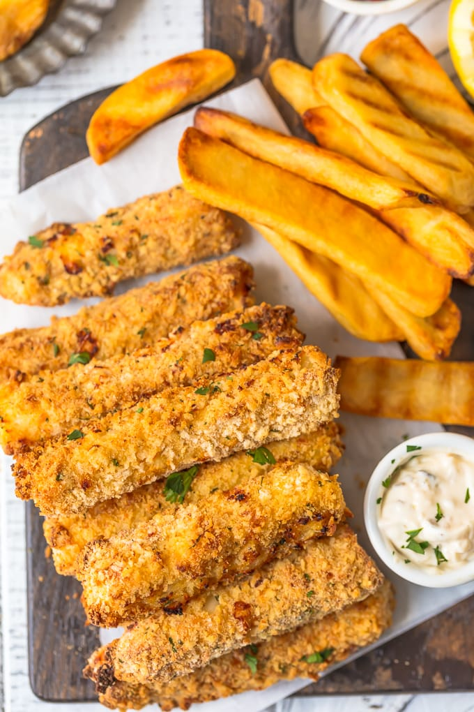 Fish sticks and thick fries on a wooden platter
