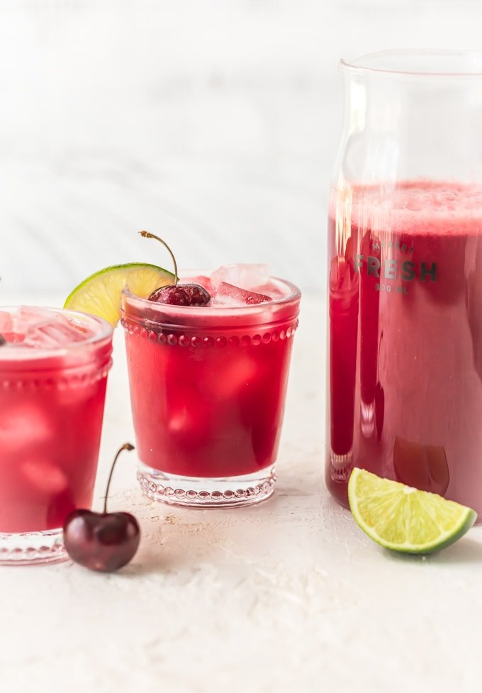 A pitcher of red cherry limeade next to two full glasses