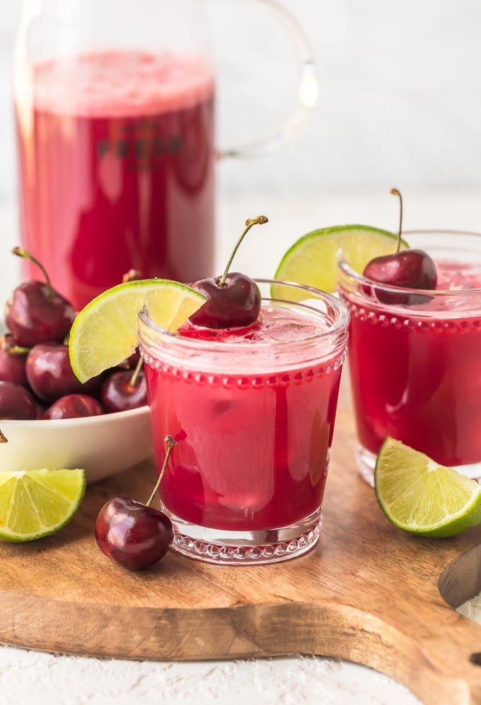 Two glasses of red cherry limeade next to a bowl of cherries