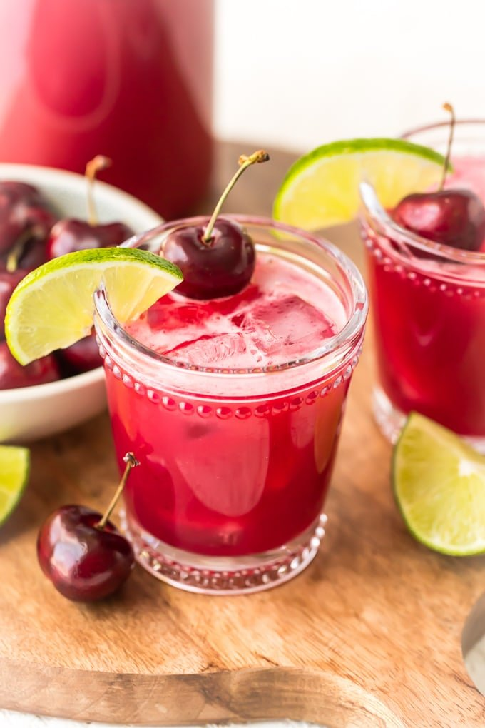 How to make cherry limeade: red drink in two glasses topped with cherries and limes