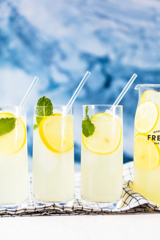 3 glasses filled with freshly squeezed lemonade, lemon slices, and mint