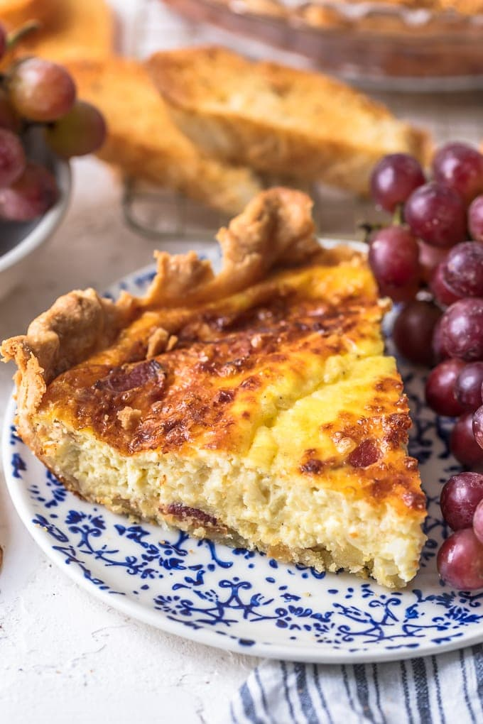 slice of quiche on a plate with grapes