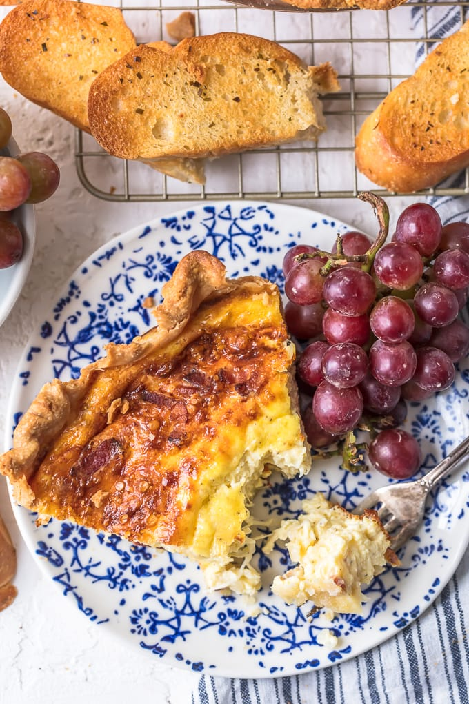 Partially eaten Quiche on a blue and white plate with grapes