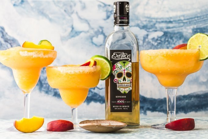 This Skinny Peach Frozen Margarita is Summer in a glass! I love the bright flavor of a delicious Peach Margarita, but lightened up in Skinny Margarita form. This cocktail is made with simple ingredients such as frozen peaches, peach sparkling water, agave nectar, lime juice, and of course, Tequila! There's no better way to celebrate Summer than with these perfect fruity Frozen Margaritas!