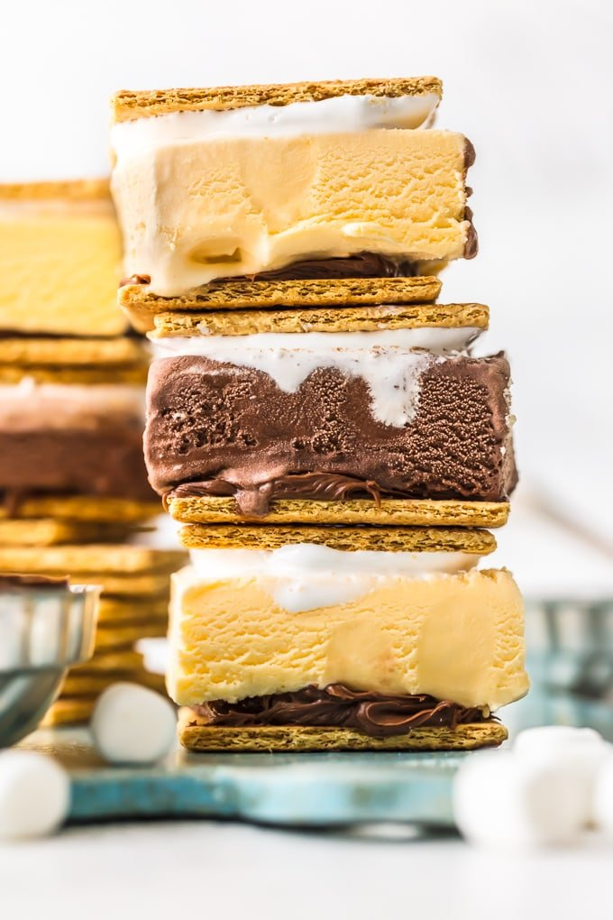 This S'mores Ice Cream Sandwich Recipe is the perfect SUPER EASY Summer Recipe. Beat the heat with ice cream, chocolate frosting, and marshmallow fluff all frozen between two graham crackers. Kids go crazy for this fun and simple Ice Cream Sandwiches hack. Nothing beats an ice cold s'more on a hot Summer day!