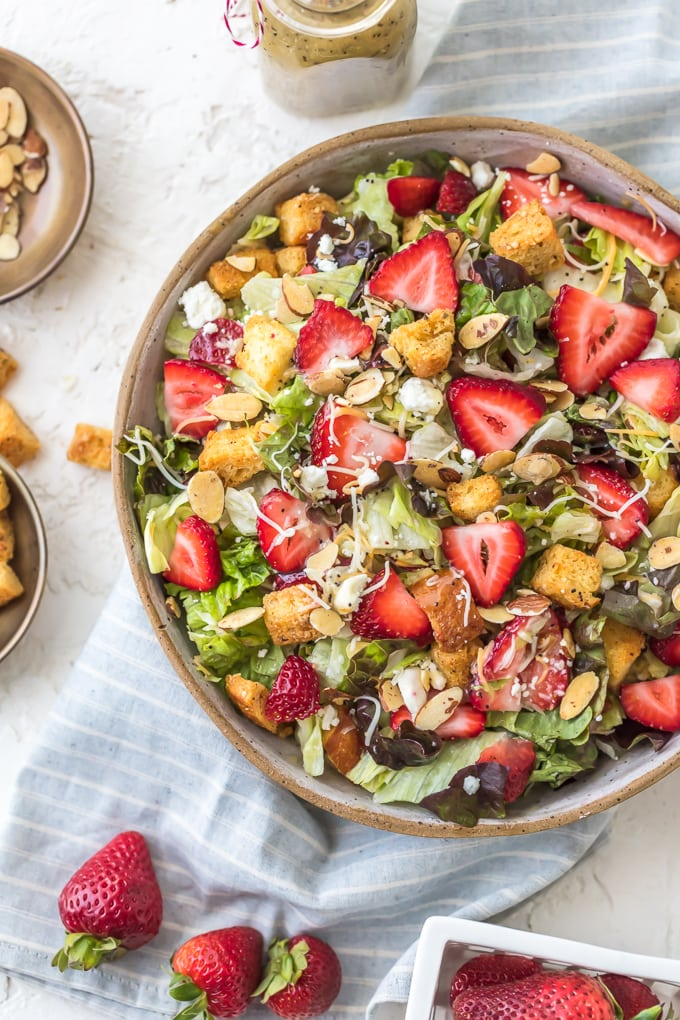 Big bowl of salad filled with strawberries, feta, lettuce, almonds, and croutons