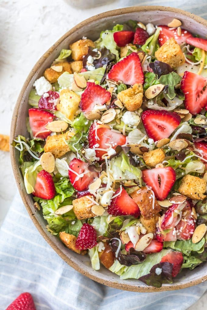 Strawberry Poppyseed Salad topped with fresh strawberries, croutons, feta, and more