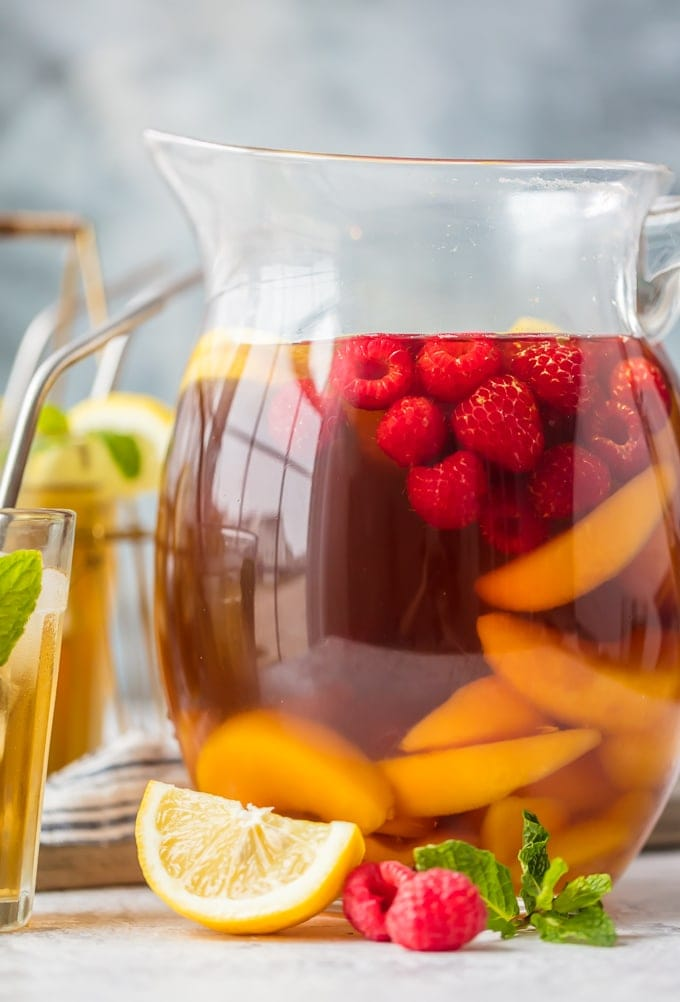 A pitcher of sweet tea sangria filled with raspberries and peaches