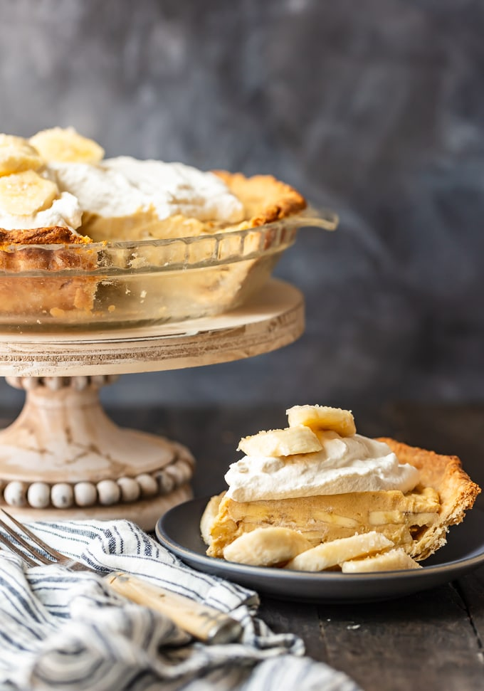 A full banana cream pie on a pedestal, next to a plate of a slice of pie