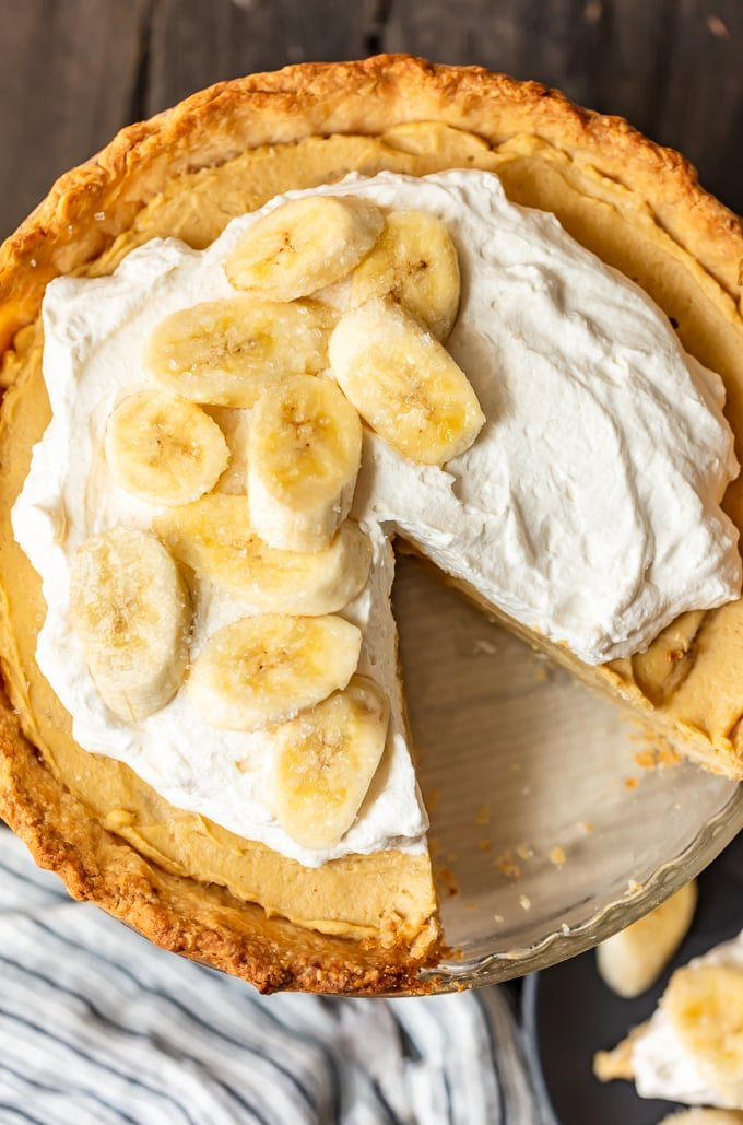 A banana cream pie topped with whipped cream and sliced bananas