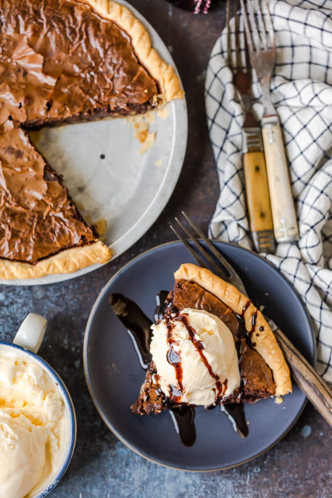 A brownie pie next to a plate with a slice of pie