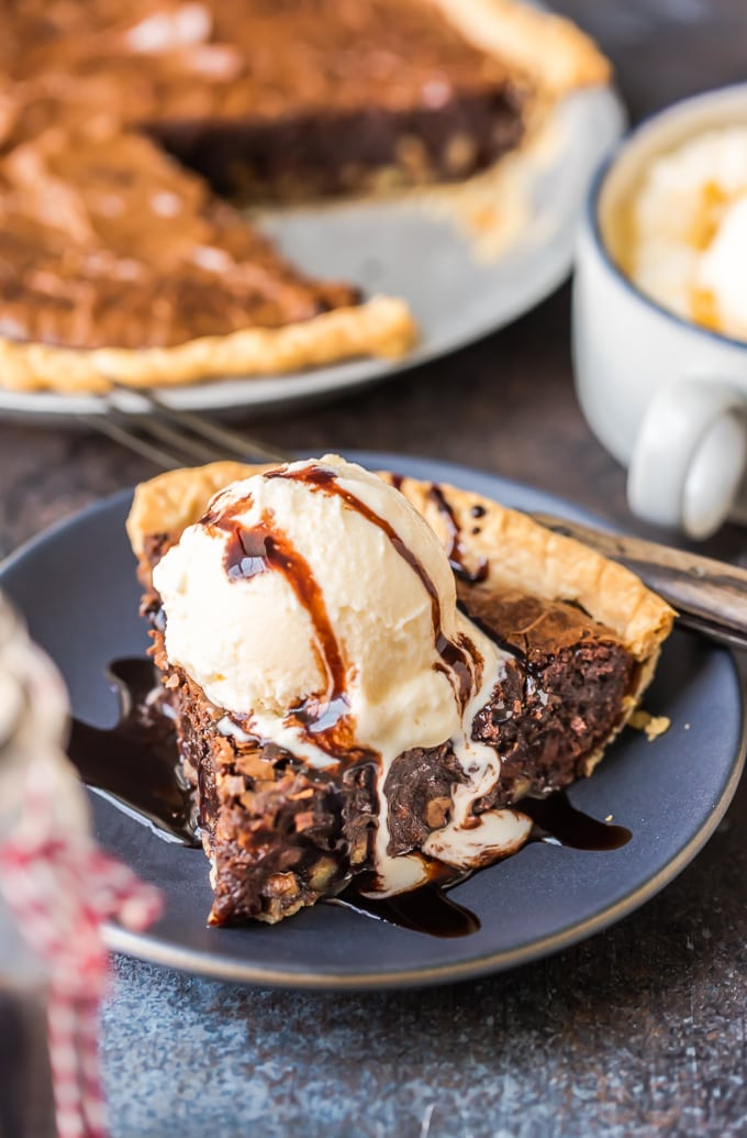 A slice of brownie pie topped with vanilla ice cream and chocolate syrup