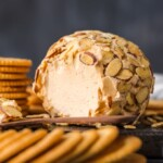 cheese ball on plate with crackers surrounding it