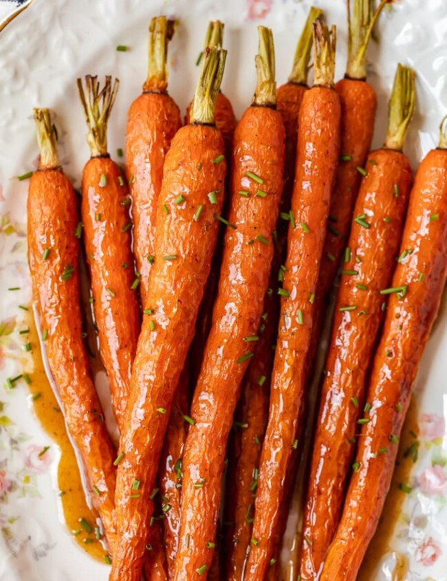 Honey Glazed Carrots with Ginger are sweet, aromatic, and absolutely tasty. This easy carrot side dish goes well with chicken, pork, or any holiday meal. I love these healthy honey roasted carrots because the flavor is so simple yet so amazing. This honey glazed carrots recipe should definitely be your next side dish!