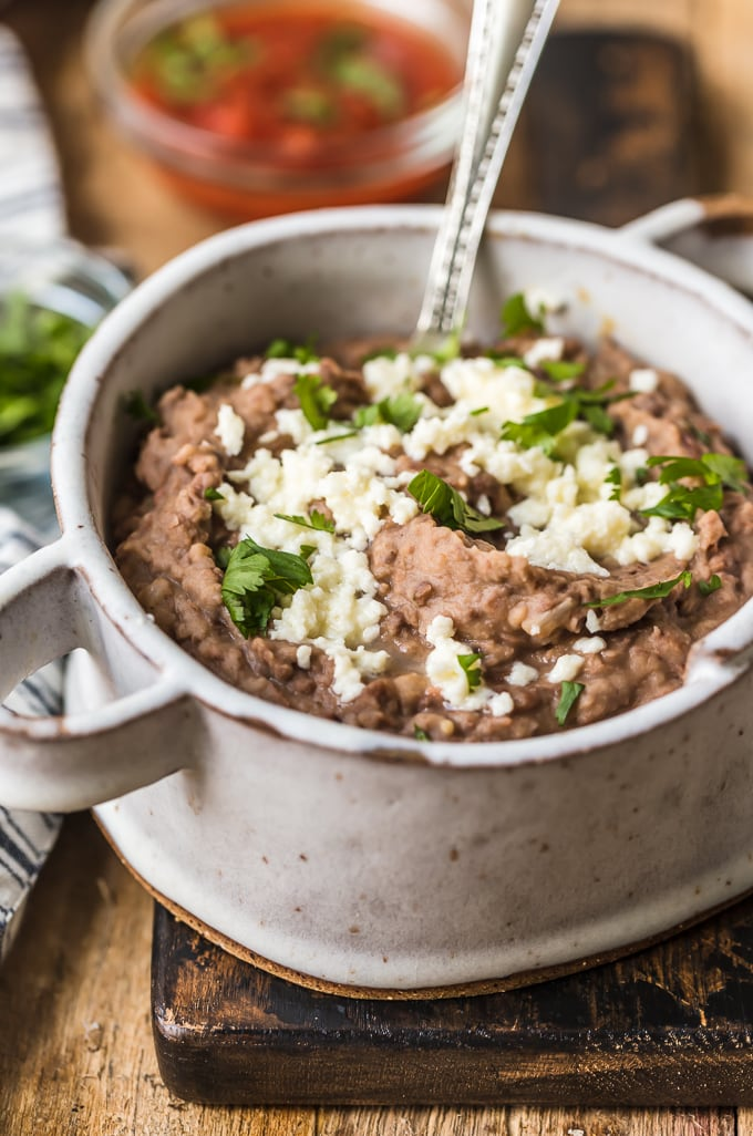 Refried beans in a serving bowl topped with cheese and cilantro