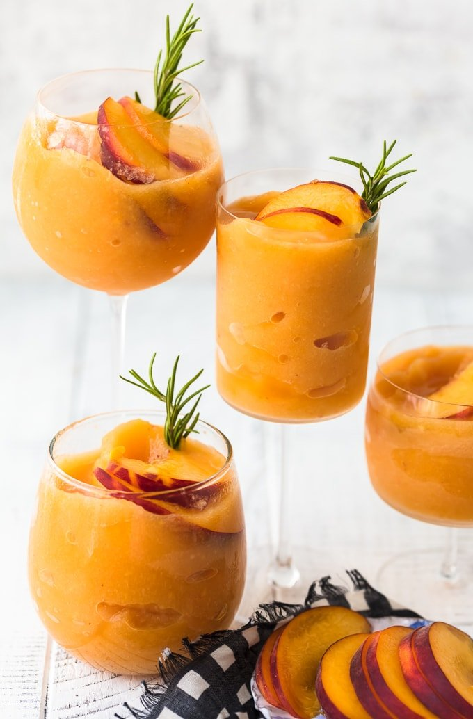 Peach Frozen Rose in different glasses with peaches