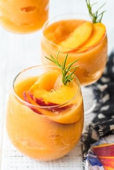 This Peach Frosé Recipe is a cocktail you definitely need for this hot Summer heat! All you need is frozen peaches, some Rosé wine, and a little honey. Frozen Rose is such a quick and easy fun cold drink to throw together for parties, friends and family, or just a quiet afternoon at home. We will show you how to make Frose and spice things up with this Peach Frose Recipe. So delicious, easy, fresh, and fun!