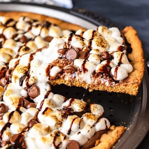 S'mores Dessert Pizza is a sweet, chocolaty dessert made just like a pizza! It's got the classic s'mores flavor of melted chocolate, graham crackers, and fluffy marshmallows, all melted together into the most amazing s'mores pizza. This easy dessert pizza recipe is fun to make and even more fun to eat!