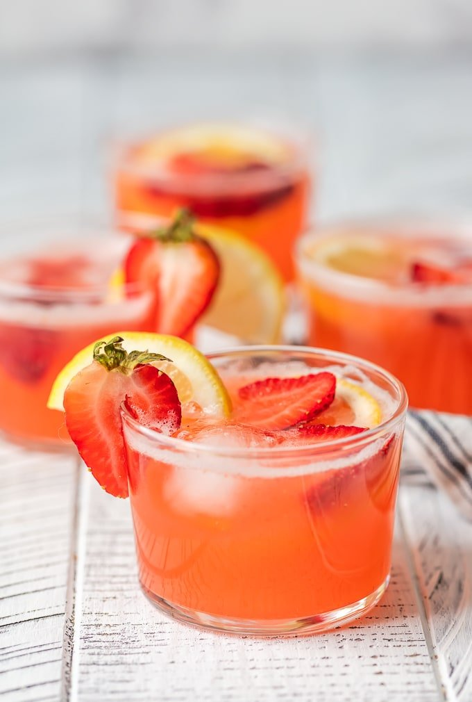 Glasses of strawberry lemonade punch garnished with fresh slices of lemon and strawberries